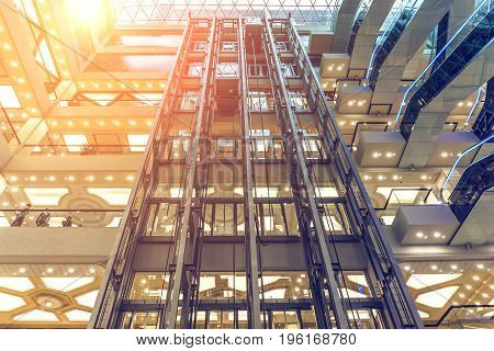 Interior of a modern multi-storey shopping center or mall, look up, floors and elevators, Sun effect, toned