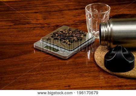 Coffee beans on the digital scale on wooden background.