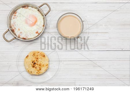 Fried egg, coffee and arepa on wooden white table
