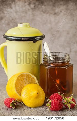 Prevention and treatment of influenza and colds. Ripe raspberries, fresh lemon, a glass jar with honey and a high mug with hot tea on a light background.  Used in folk medicine.