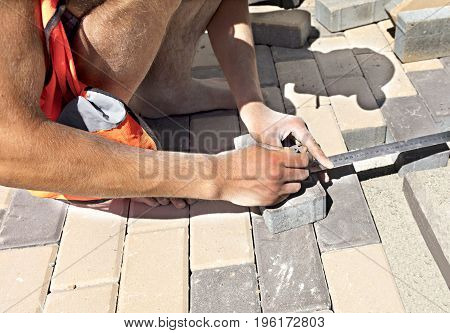 The worker measures a bar of sidewalk tiles for the final laying on the terrace