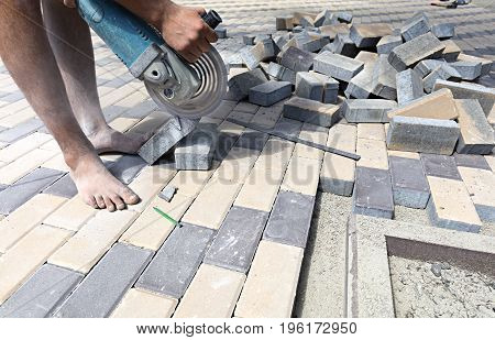 The worker cuts a bar of paving slabs for the final laying on the terrace