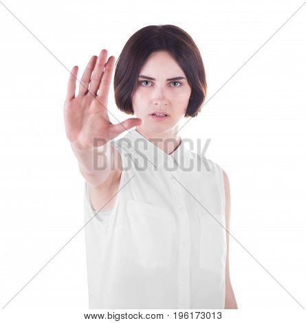 Close-up of an angry female is making stop gesture, isolated on a white background. A serious young brunette woman with stop sign. Business woman in elegant clothes making stop sign.