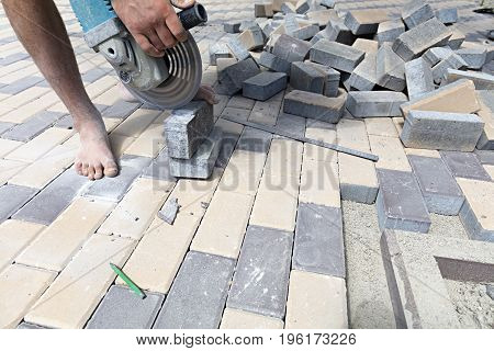 The worker cuts a bar of paving slabs for the final laying on the sidewalk