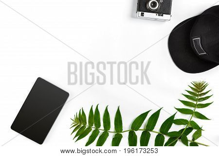 Travel accessories set on white background: smart, cap and camera. Top view point. Flat lay. Still life. Copy space