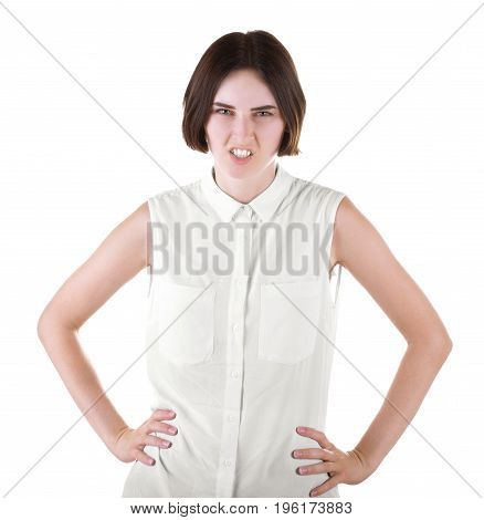 An angry lady with hands on hips. A posing brunette girl isolated over the white background. A gorgeous though disgusted woman standing in a light blouse. Communication problems.