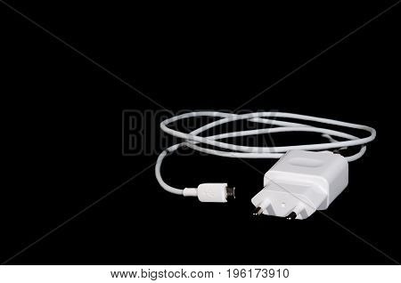 White cell phone charger, isolated on black background. Selective focus.