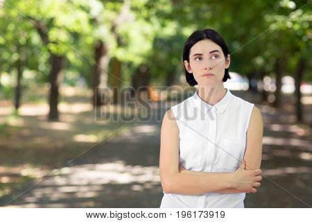 A thoughtful gorgeous lady posing on a natural green background. A casual young woman in a sunny summer park. A concerned girl with her hands crossed wearing a white blouse.