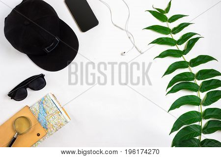 Travel accessories set on white background: smart, headphones, cap, map and sunglasses. Top view point. Flat lay. Still life. Copy space