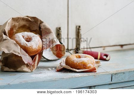 Homemade donuts with sugar powder from paper bag served with vintage sieve on blue wooden table. Rustic style, day light.