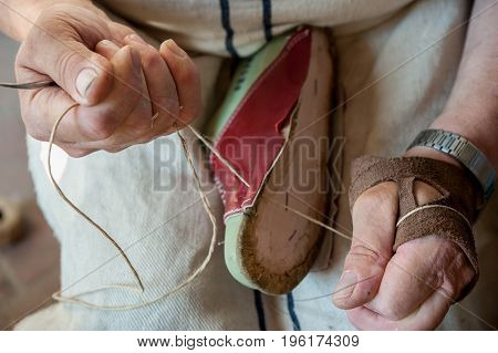 The shoemaker sews a shoe craftily with twine