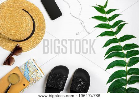 Travel accessories set on white background: smart, headphones, hat, map and sunglasses. Top view point. Flat lay. Still life. Copy space