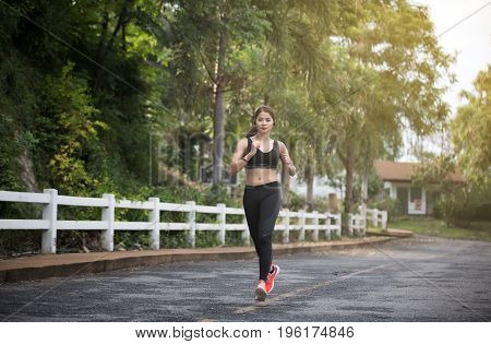 Running woman. Female runner jogging during outdoor on road .Young mixed race girl jogging