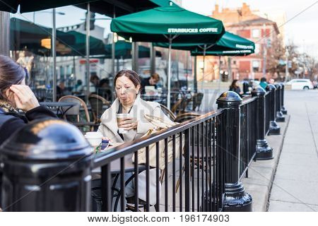 Washington Dc, Usa - February 5, 2017: Woman At Starbucks Sitting Outside Looking At Coffee Cup Maki