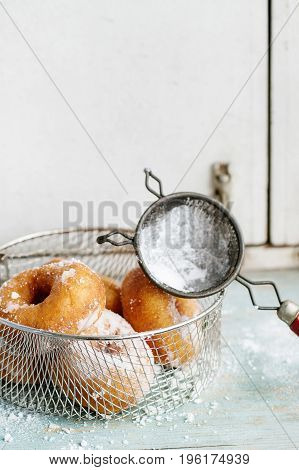 Homemade donuts with sugar powder in frying basket served with vintage sieve on blue wooden table. Rustic style, day light.