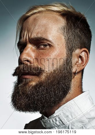 Portrait of hipster bearded man's side face. Man in plaid shirt with short hair on sides posing near grey background.