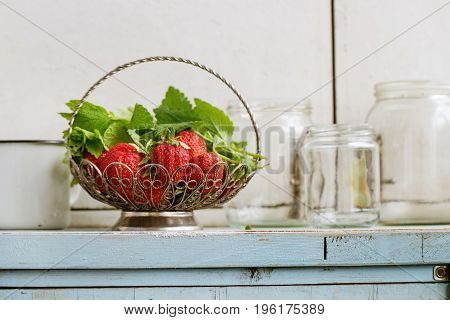 Fresh ripe garden strawberries and melissa herbs in vintage vase standing with empty glass jars for jam on blue white wooden kitchen table. Rustic style, day light, copy space