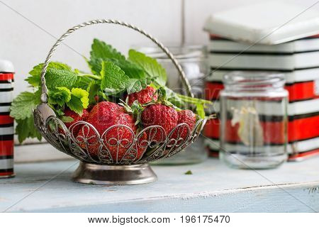 Fresh ripe garden strawberries and melissa herbs in vintage vase standing with empty glass and metal jars for jam on blue white wooden kitchen table. Rustic style, day light, copy space