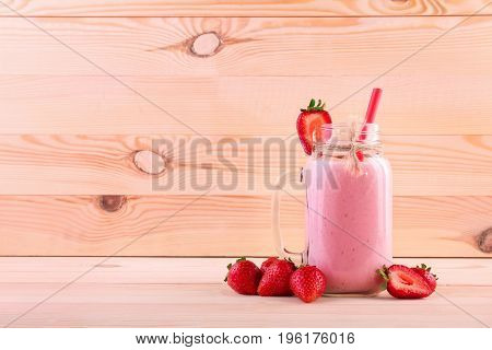 Organic and fresh strawberry yogurt in a mason jar with red straw on a light brown wooden background. A mason jar with handle and red straw filled with a pink strawberry smoothie and berries around.