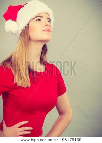 Xmas seasonal clothing winter christmas concept. Young woman wearing Santa Claus helper costume thinking about holiday celebration.