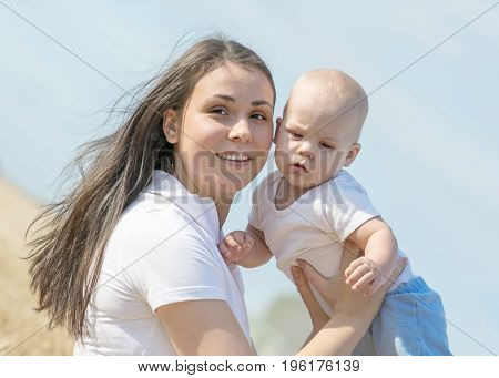 Young happy mother playing with her adorable baby boy