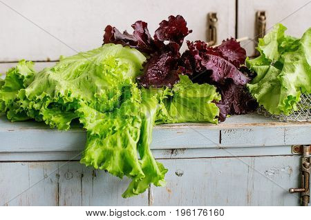 Fresh green and purple leaf salad over old blue white wooden kitchen table. Rustic style, day light.