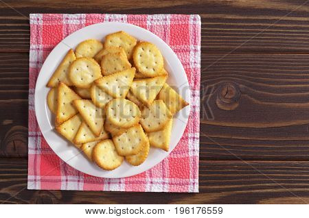 Crackers biscuits with cheese flavor in plate on wooden table top view