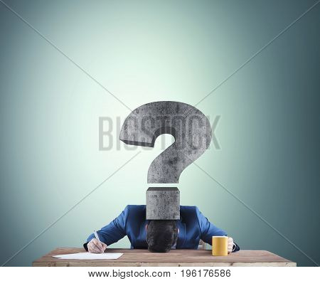 Business man pressed by a question mark onto desk and trying to write something.
