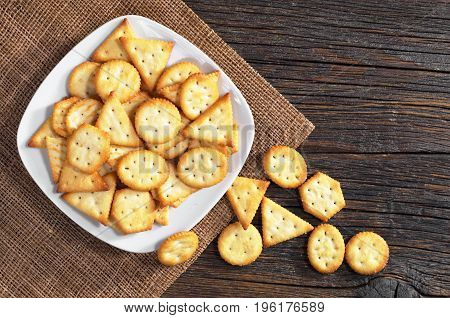 Crackers biscuits with cheese flavor in plate on dark wooden background top view