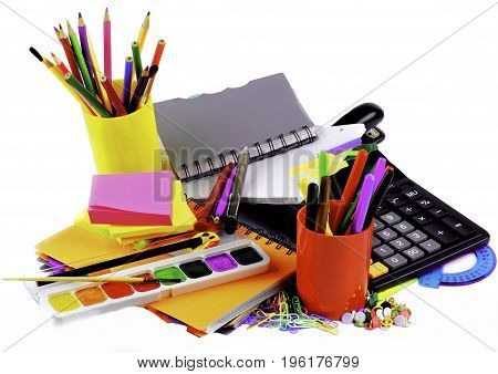 School Supplies Concept with Various Colorful Ballpoint Pens Pencils Felt Tip Pens Pencil Sharpener Watercolor Paints Paper Clips Calculator and Sticky Notes closeup on White background