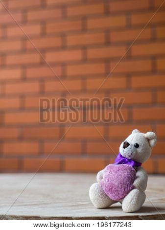 Teddy bear holding a purple heart. Placed on a wooden desk. The backdrop is a brick block of brown.