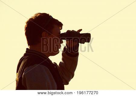Silhouette Of Man Watching Sunset With Binoculars