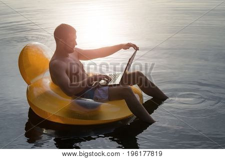Man With Laptop On A Rubber Ring In The Water At Sunset, Free Space.
