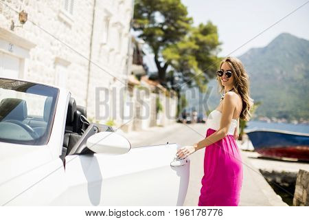 Young Attractive Woman Poses Next To A  Cabriolet At Seaside