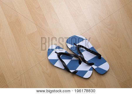 Bavarian thongs on brown floor, travel background