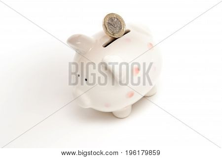 Piggy Bank With Coin Being Placed In For Savings