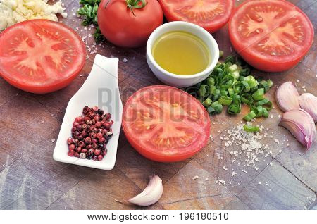tomatoes herb garlic and oil arranged on wooden plank