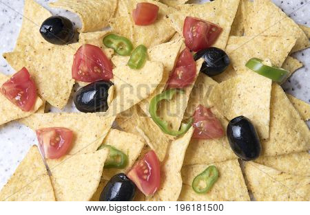 Close up image of nachos with olives, tomatoes and jalapeno peppers