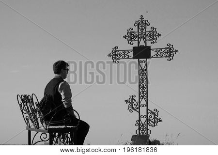young man sit near the grave of his friend or relative