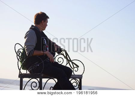 young man relax on a bench in a park