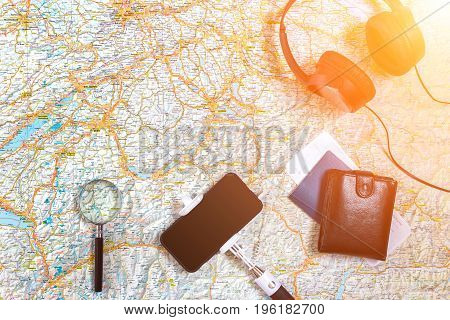Accessories for travel. Passport, headphones, smart phone and travel map. Top view. Holidays and tourism concept. Copy space. Still life. Flat lay. Sun flare