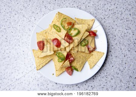Nachos with tomatoes and jalapeno peppers on a white plate