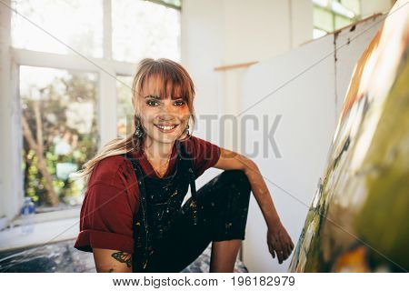 Indoor shot of professional female painter in studio. Woman artist making a painting on canvas in her workshop.