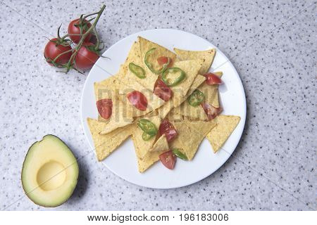 Nachos on a white plate surrounded with avocado and  tomatoes