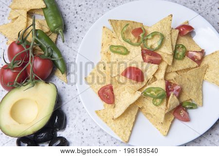 Nachos on a white plate surrounded with avocado, tomatoes, peppers, and olives