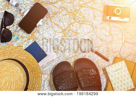 Accessories for travel. Passport, hat, smart phone and travel map. Top view. Holidays and tourism concept. Copy space. Still life. Flat lay. Sun flare
