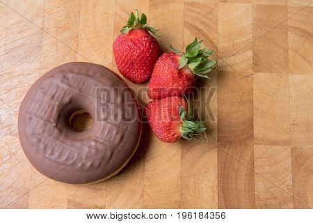 Chocolate donuts on a wooden background with strawberries