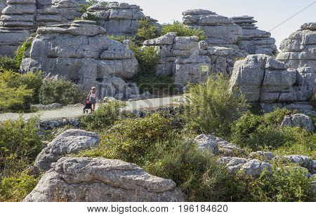 Antequera Spain - July 14 2017: elderly woman walking by Torcal Natural Park with four-wheeled walker Malaga Spain
