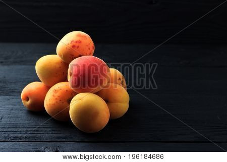 Apricot folded in a heap on a black wooden background