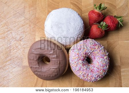Strawberry, chocolate and jam donuts on a wooden background with strawberries